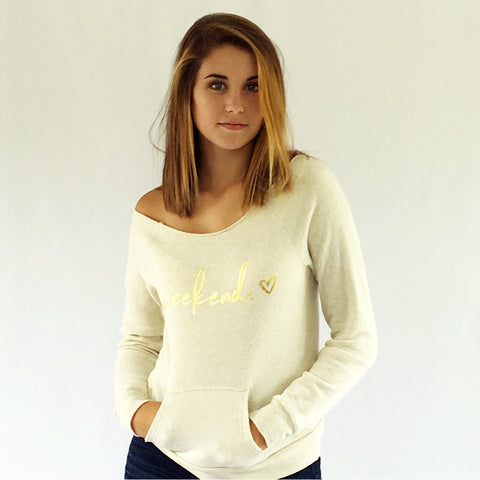 "One PLane Jane Golden Weekend Sweatshirt. Shown in wheat with gold-leaf print ""Weekend"" featuring a heart next to the word.  Scoop neckline with off the shoulder look. Front hand pouch."
