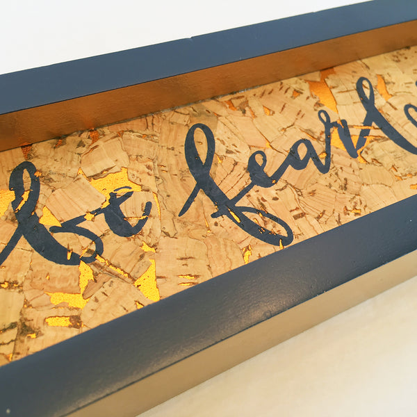 "Be Fearless box sign view from front close up. Navy wood frame with cork inset with gold accents.  ""Be Fearless"" in blue"