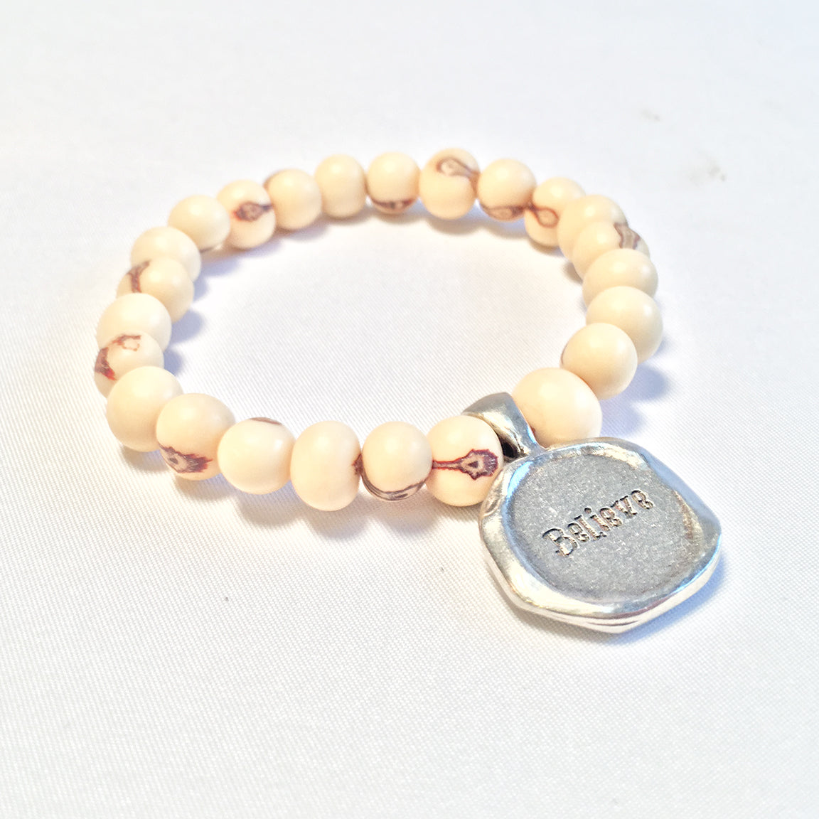 "Believe Acai Seed White Beaded Bracelet. Pewter ""believe"" charm"