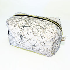 One Plane Jane Cosmetic bag and Travel Pouch. Quilted Cream fabric with world map and airplanes.  Zippered top closed.