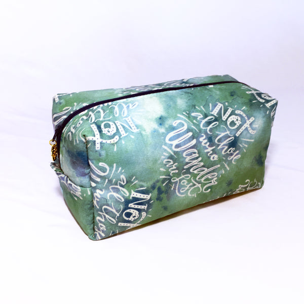 "One Plane Jane Cosmetic bag and Travel pouch. Green and blue cotton fabric with the saying ""Not all who wander are lost"". Zippered top closed."
