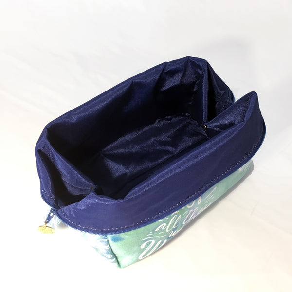 "One Plane Jane Cosmetic bag and Travel pouch. Green and blue cotton fabric with the saying ""Not all who wander are lost"". Zippered top open with sides folded over revealing blue polyester interior"
