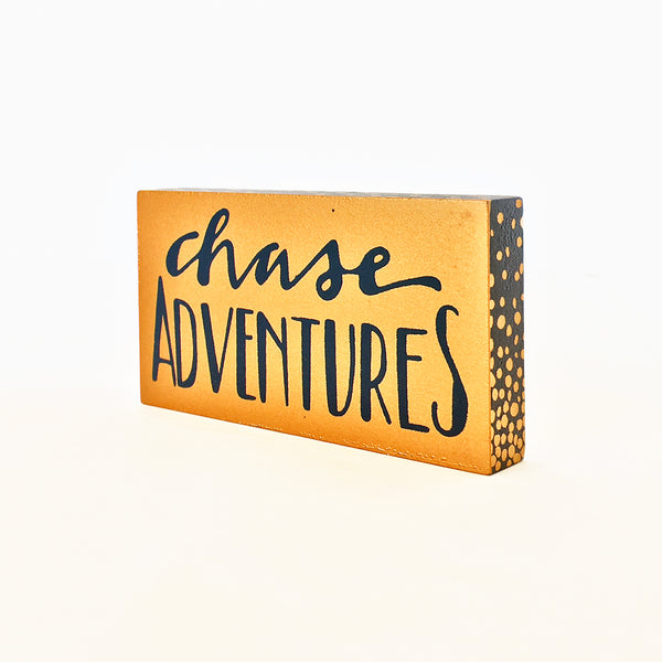Chase Adventures magnet. Gold block with blue writing. Sides of block navy with gold dots.