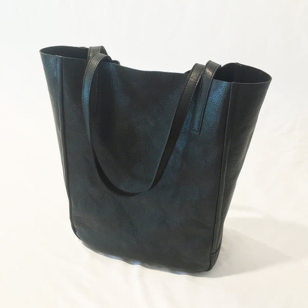 One Plane Jane Delta Travel tote in black leather.  Front view with straps folded over and handing down.