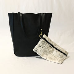 One Plane Jane Delta Travel tote in black leather.  Front view with straps folded over and handing down and the key strap out with the zippered pouch attached. Pouch made from world map and airplane fabric