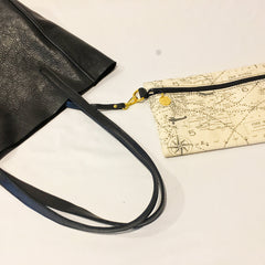 One Plane Jane Delta Travel tote in black leather.  Closeup view with straps folded over and handing down and the key strap out with the zippered pouch attached. Pouch made from world map and airplane fabric