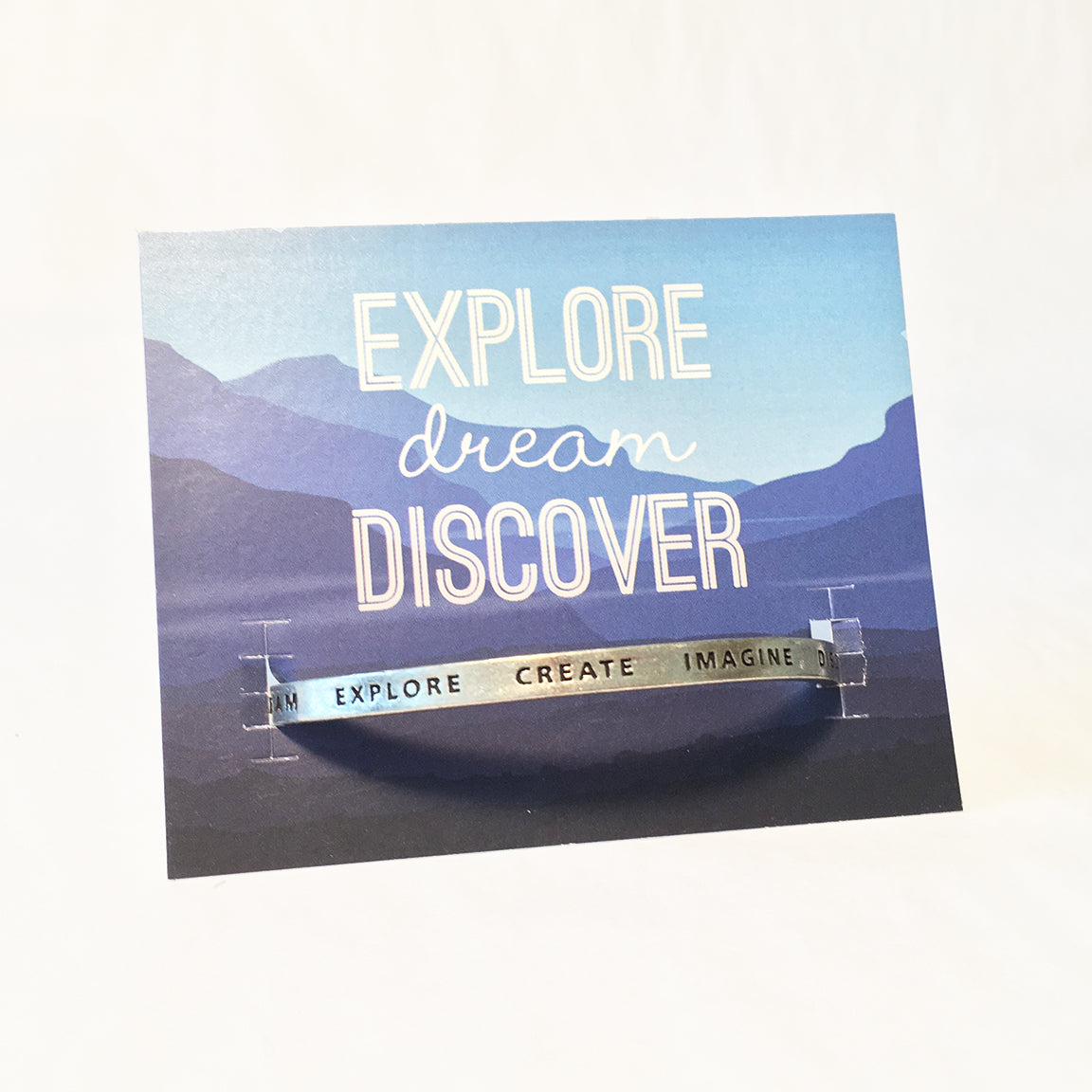 Adjustable cuff bracelet on a backer card with a mountain picture. Cuff has engraved words Dream Explore Create Imagine Discover