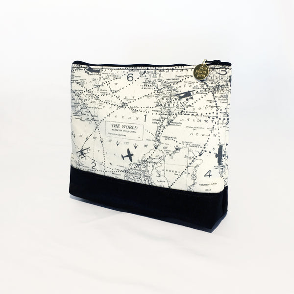 One Plane Jane Airplane Small Cosmetic bag pouch. Cream and black design featuring the world map with airplanes.  Zippered top and One Plane Jane zipper charm.
