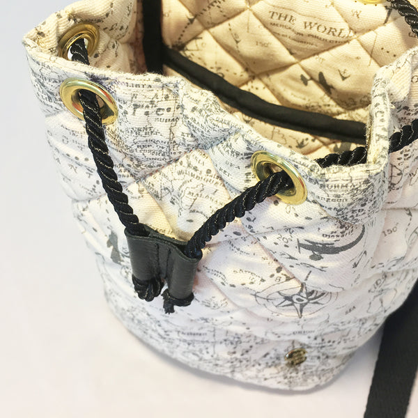One Plane Jane Headset Bag & Bucket Purse. Black Cross body strap. Top view with black leather flap open and airplanes on a world map design. Quilted cotton.