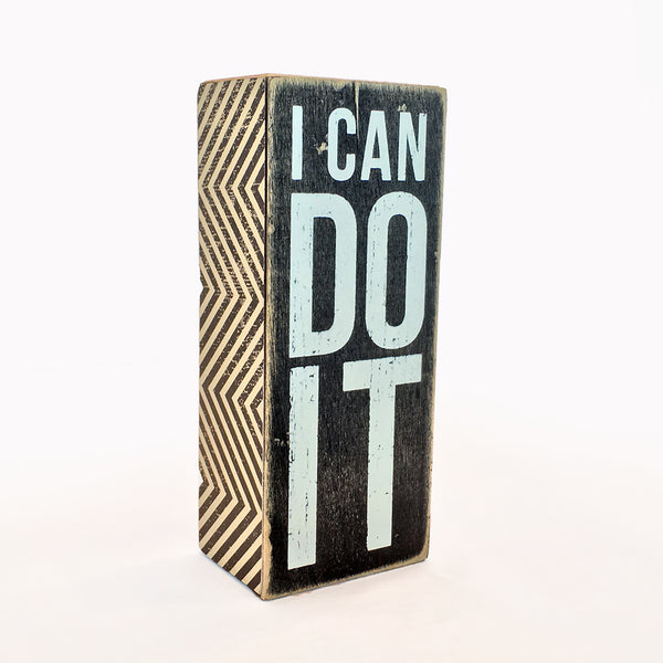 I CAN DO IT box sign black with white writing.  Box sides with angular graphic line art black and white.