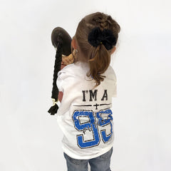 One Plane Jane I'm A Future 99 Girls T-shirt. Shown on a little girl back view. Football jersey style with bright blue and black letters