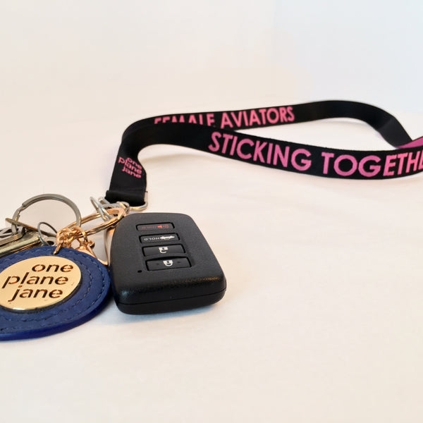 One Plane Jane and Female Aviators Sticking Together Lanyard.  Black with Pink text. Silver clip. Shown with keys