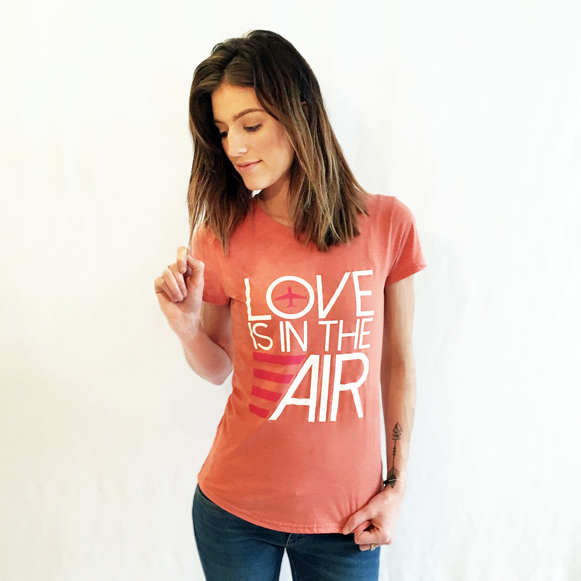 One Plane Jane Love Is In The Air featuring an airplane. Heather Bronze t-shirt.  Large graphic design with white and pink ink