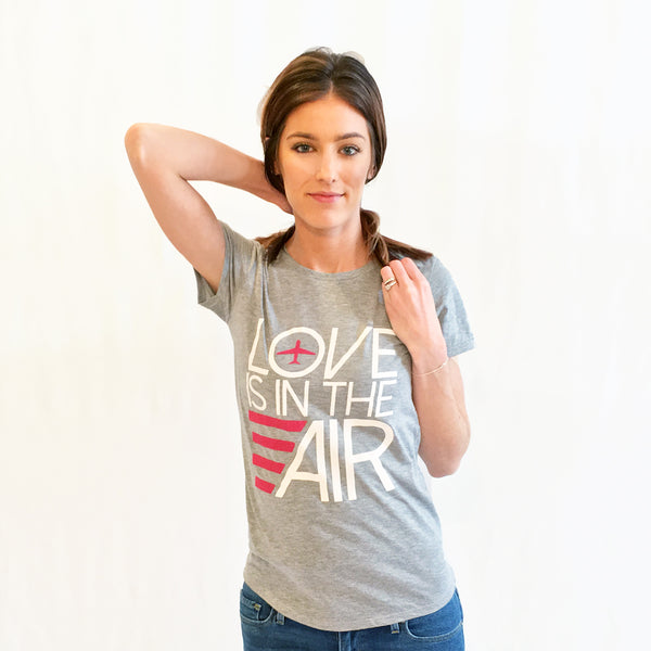 One Plane Jane Love Is In The Air featuring an airplane. Grey crew neck t-shirt.  Large graphic design with white and pink ink