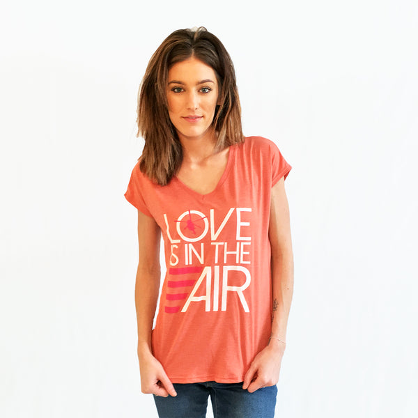 One Plane Jane Love Is In The Air featuring a Helicopter. Heather Bronze tee.  Large graphic design with white and pink ink