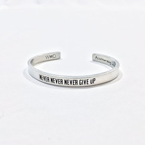 "One Plane Jane adjustable Pewter cuff with quote ""Never Never Never Give Up"""