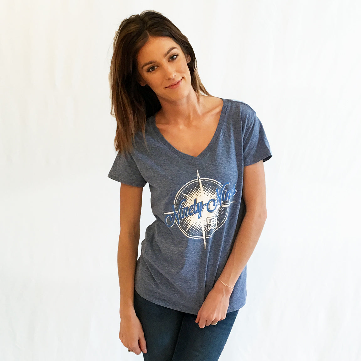 One Plane Jane & Ninety-Nine Logo shirt. Cosmic blue V-neck t-shirt with white compass and blue words (Ninety-Nines).  Ninety-nine logo embedded in design
