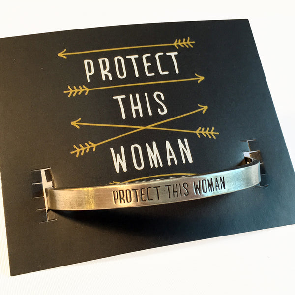 "Protect This Woman Pewter adjustable cuff bracelet with backer card.  ""Protect This Woman"" displayed on face of bracelet."