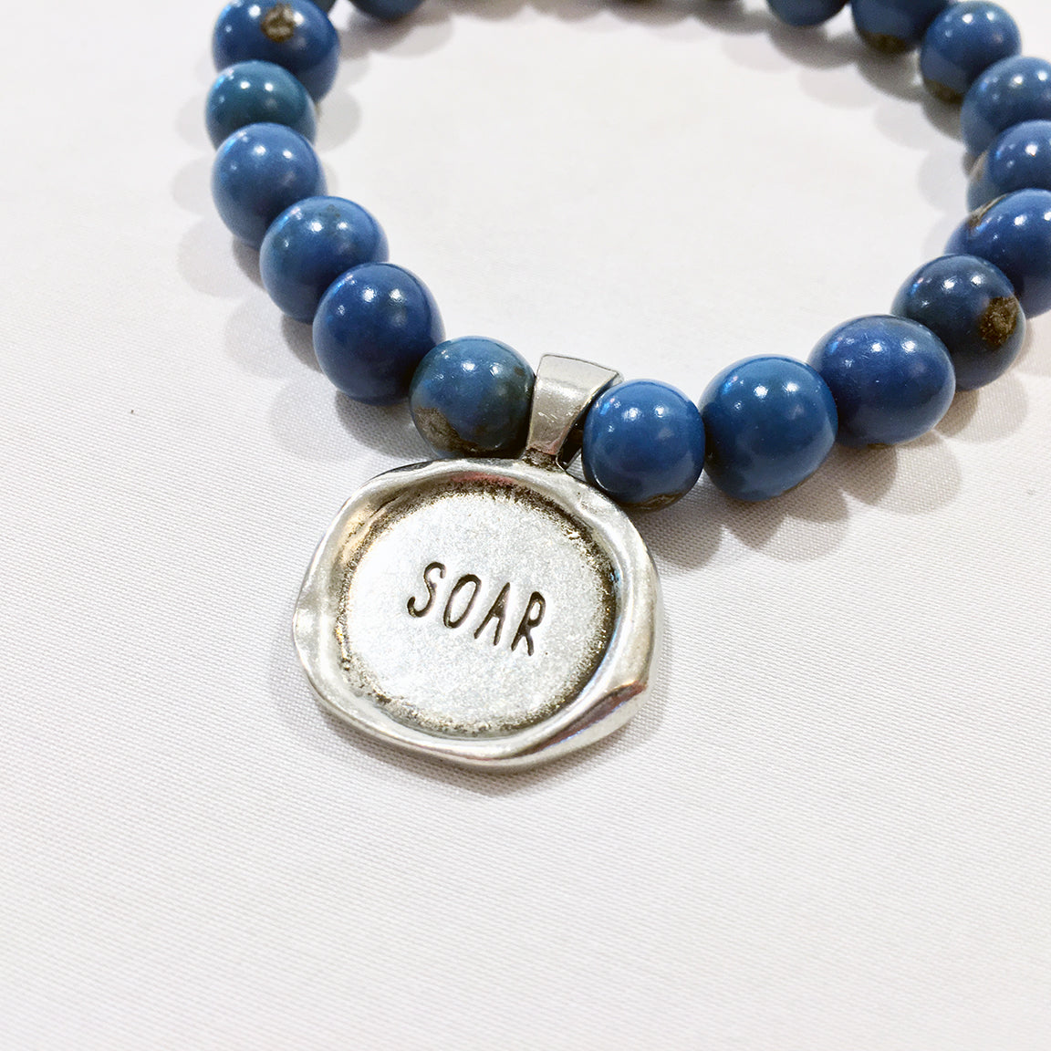 "One Plane Jane Denim blue acai bead bracelet with a pewter seal charm featuring the word ""Soar"""
