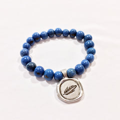 One Plane Jane Denim blue acai bead bracelet with a pewter seal charm featuring a feather
