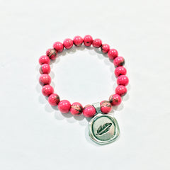 One Plane Jane pink acai bead bracelet with a pewter seal charm featuring a feather