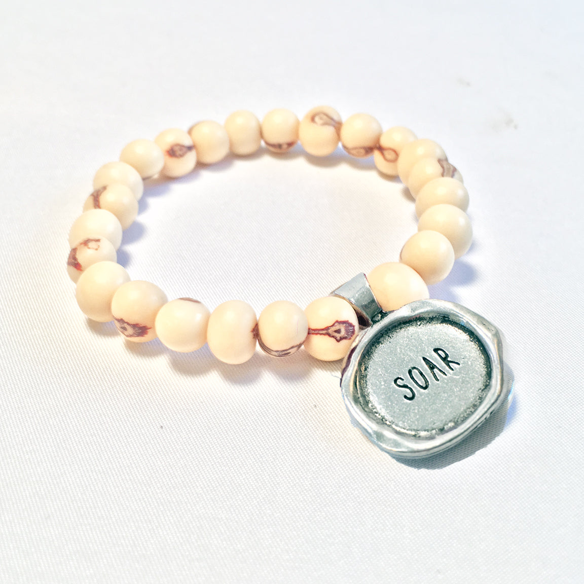 "One Plane Jane white acai bead bracelet with a pewter seal charm featuring the word ""Soar"""