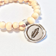 One Plane Jane white acai bead bracelet with a pewter seal charm featuring a feather
