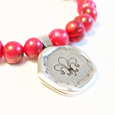 Acai seed beaded bracelet with pewter strength symbol charm. Red/pink color