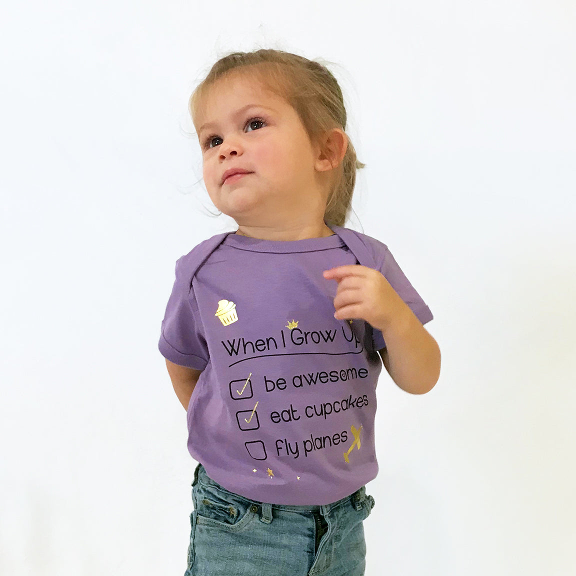 One Plane Jane bucket list When I Grow Up Infant Onesie T-shirt. Shown in purple with black writing and gold accents including an airplane. Already checked, Be Awesome & Eat Cupcakes. WAiting to check, Fly Planes.