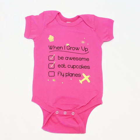 One Plane Jane bucket list When I Grow Up Infant Onesie T-shirt. Shown in pink with black writing and gold accents including an airplane. Already checked, Be Awesome & Eat Cupcakes. WAiting to check, Fly Planes.
