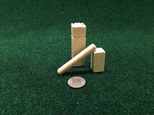 image of a mini kubb pieces compared to a quarter