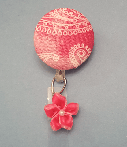 This pink bandana cover button is perfect for anyone who wants to add a little extra style to their badge! This badge includes a pink nylon snap-button bow with faux pearl.  *Handmade item, bandana fabric design, cover button, pink snap-button bow, clear retractable badge reel with alligator clip.