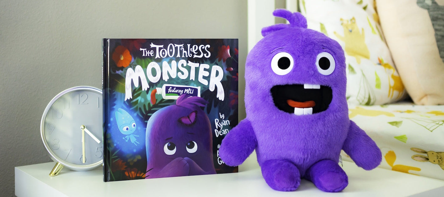 The Toothless Monster purple plush toy with hardcover Tooth Fairy book. Next to bed sitting on night stand.
