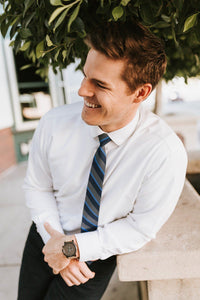 man in white shirt leaning against bench with grey navy striped tie