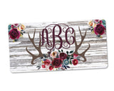 Personalized Monogram Aluminum License Plate with Red Rose Antlers over White Wood Background