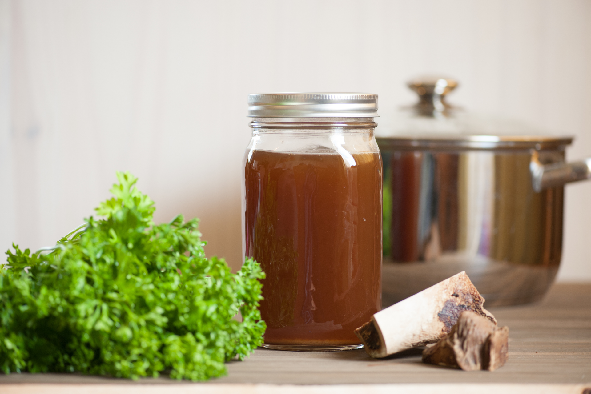 Ostrich bone broth in a jar with parsley