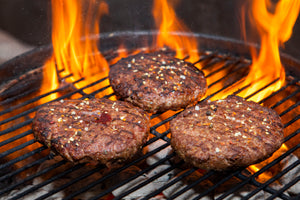 3 ground ostrich steak patties on grill