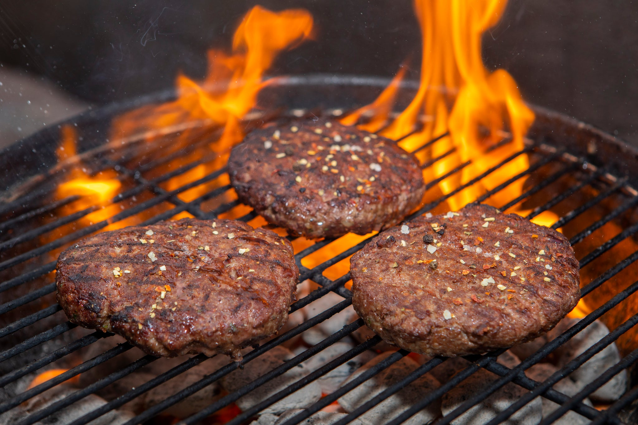 3 ground ostrich steak burgers being flame grilled