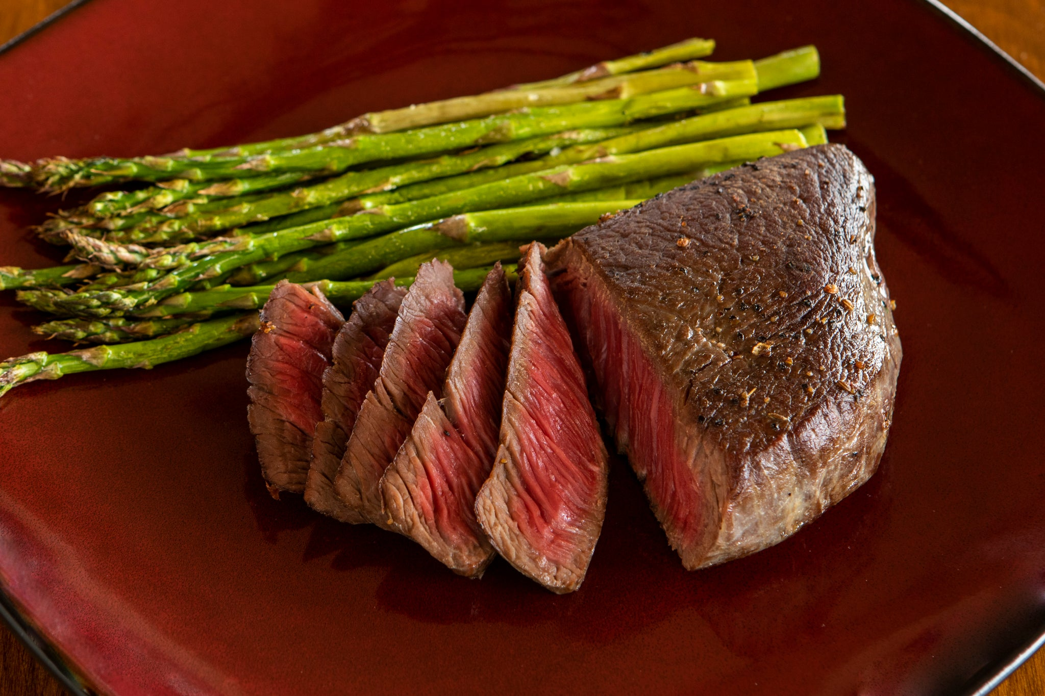 sliced cooked ostrich fan filet next to asparagus