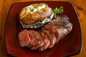 cooked and sliced ostrich top loin with baked potato