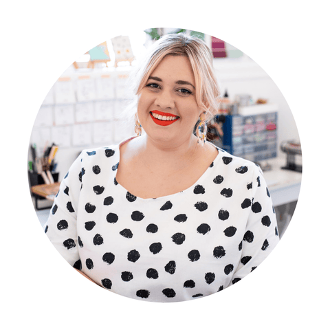 Hayley sits in a bright office space, looking at the camera and smiling. She is a blonde, white woman and is wearing a white spotty dress and bright red lipstick.