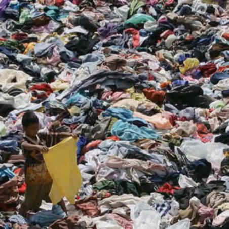 Sea of discarded clothing in landfill with small child picking through it