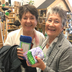 Two ladies buying locally-made knitted kitchen cloths