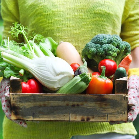Lady holding wooden tray of fresh produce