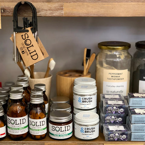 Zero waste toothpaste options on a shelf, including jars of toothpaste tablets, tooth powder and tooth soap