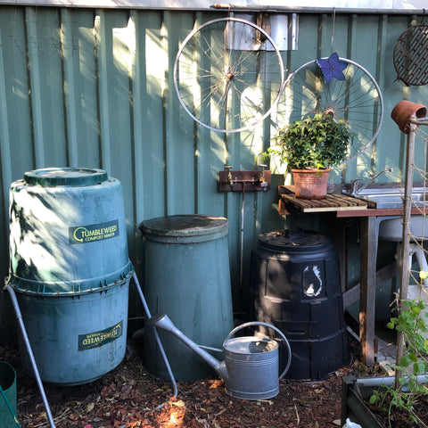 Back yard with various compost bins including a tumbler compost and cold compost mound
