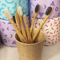 Bamboo toothbrushes in a cup with a colourful background