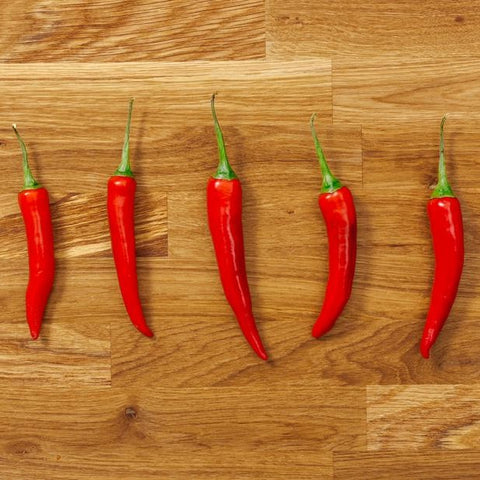 Chillies lined up on a chopping board