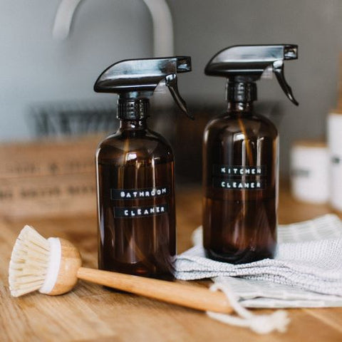 Natural cleaning with two glass spray bottles and a wooden cleaning brush
