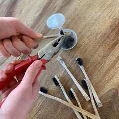 Bamboo toothbrush plastic bristles being easily removed with pliers and placed inside a plastic container